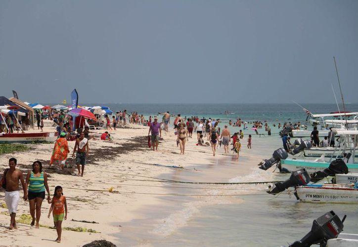 Los arenales de Puerto Morelos lucieron llenos de bañistas el primer domingo de vacaciones de Semana Santa. (Miguel OrtÍz/SIPSE)