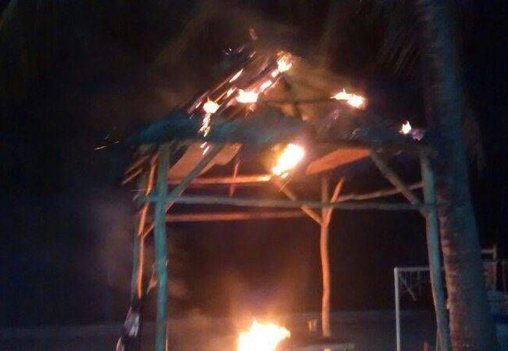 Durante los primeros minutos de este viernes una palapa que funcionaba como módulo turístico fue incendiada.  (Rossy López/SIPSE)