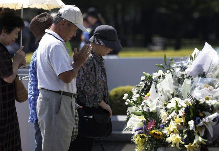 Varias personas rezan por las víctimas de la bomba atómica, delante de un cenotafio, en el Parque Conmemorativo de la Paz de Hiroshima, en el oeste de Japón. (EFE)