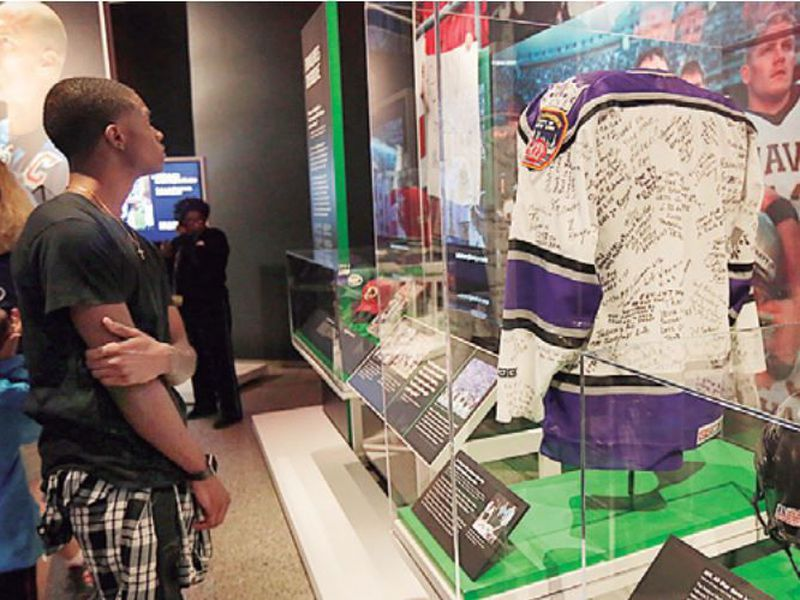 "A young to the National September 11 Memorial & Museum views the ""Comeback Season: Sports After 9/11"" exhibit, including a Los Angeles Kings hockey jersey."