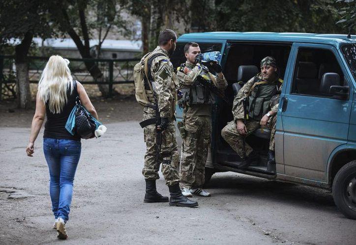 Una joven pasa cerca de unos soldados ucranianos en la ciudad de Slaviansk, Ucrania. (EFE)