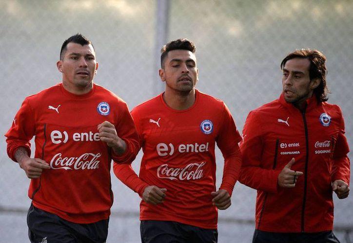 Gonzalo Jara (centro) se perderá el resto de la Copa América 2015: recibió castigo por los 'toqueteos' al uruguayo Edinson Cavani, en partido de cuartos de final del torneo. En la imagen aparecen también Gary Medel (izq.) y Jorge Valdivia. (AP)