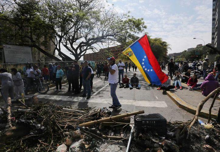 Manifestantes ondean la bandera venezolana cerca de una barricada en el barrio de La Boyera en Caracas, Venezuela. (Agencias)