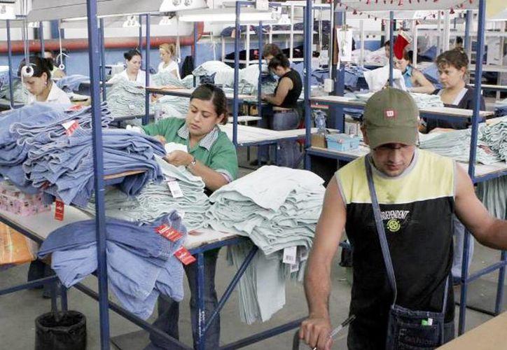 Todos los trabajadores tienen derecho a recibir el aguinaldo, y el plazo límite fue el pasado sábado 20. Imagen de un grupo de empleados de una fábrica de ropa. (Milenio Novedades)