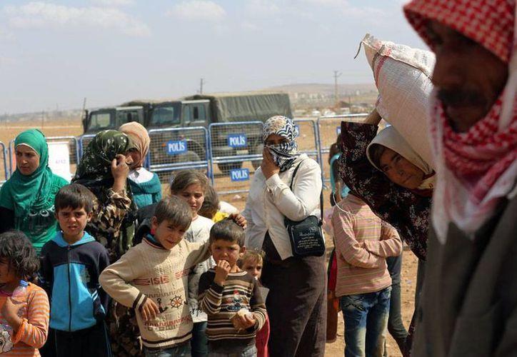 Refugiados sirios llegan a la frontera con Turquía, tras los bombardeos de EU en Kobani. Según el Gobierno de Siria, no hay apoyo para la acción militar de occidente, pero ven con buenos ojos que los ataques sean contra e Estado Islámico. (AP)