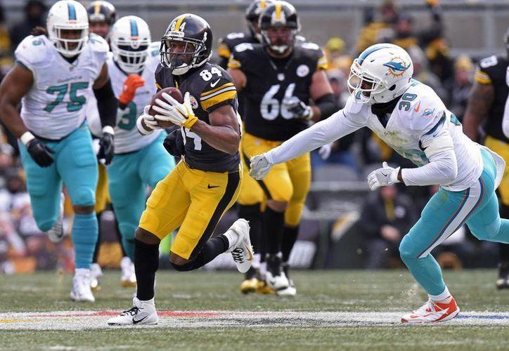 El receptor abierto de Steelers, Antonio Brown (84), se escapa a la marca de Bacarri Rambo (30), de Delfines, que fueron eliminados en la ronda de comodines de la NFL. (AP)