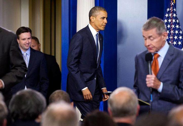 El presidente Barack Obama, seguido por su vocero Josh Earnest, arriba a la sala de prensa de la Casa Blanca para fijar su posición respecto a la iniciativa de los republicanos, en materia de migración. (Foto: AP)