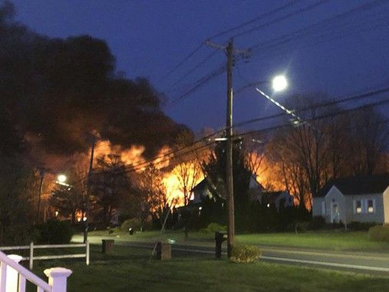This photo provided by WFSB-TV shows a fire behind a house, in North Haven, Conn. A Connecticut woman's call to police to report domestic.