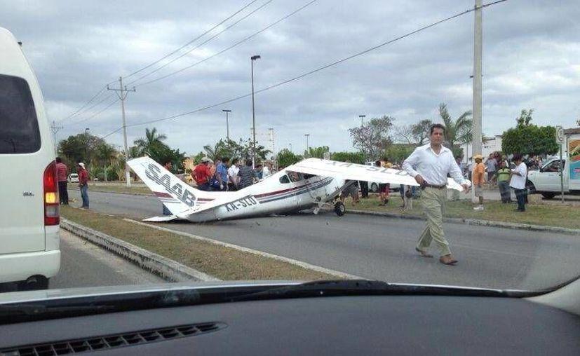 La avioneta desplomada la tarde de hoy, quedó sobre el bulevar Playa del Carmen. (Facebook Willy Rincón/SIPSE)