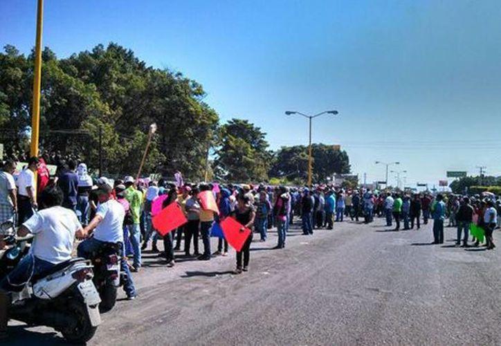 Los manifestantes amenazan con incendiar los vehículos que tienen retenidos en contra de los grupos de autodefensa. (Milenio Novedades)