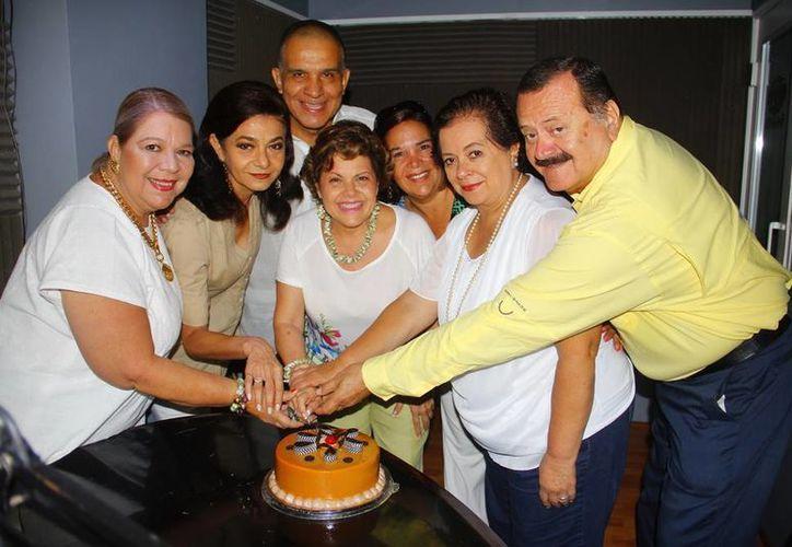 Conductores e invitados cortan el pastel de aniversario durante la emisión del programa radiofónico. (SIPSE)