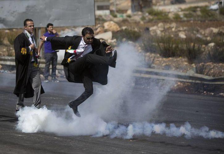 Un abogado vestido con su toga patea una lata de gas lacrimógeno de vuelta hacia soldados israelíes durante una protesta de letrados palestinos en solidaridad con manifestantes en la explanada de las Mezquitas, cerca de Ramala, en Cisjordania. (Agencias)