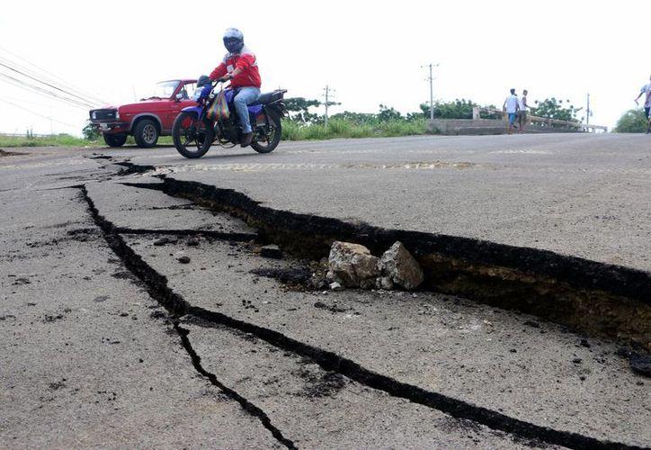 Imagen de la fractura de una carretera causada por el terremoto de 7.8 que afectó ayer a Ecuador. Hoy se registró un sismo de 5.0 grados de magnitud en la escala de Richter en el territorio salvadoreño. (Foto AP / Patricio Ramos)