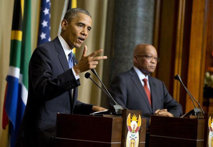 Obama se reunió durante media hora con familiares de Mandela este sábado en la mañana. En la foto aparece con Jacob Zuma, presidente de Sudáfrica. (Agencias)