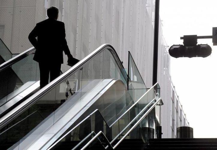 El pie izquierdo del trabajador quedó atrapado entre los escalones y la plancha metálica donde terminan. Vista de un hombre utilizando una escalera mecánica. (EFE/Archivo)