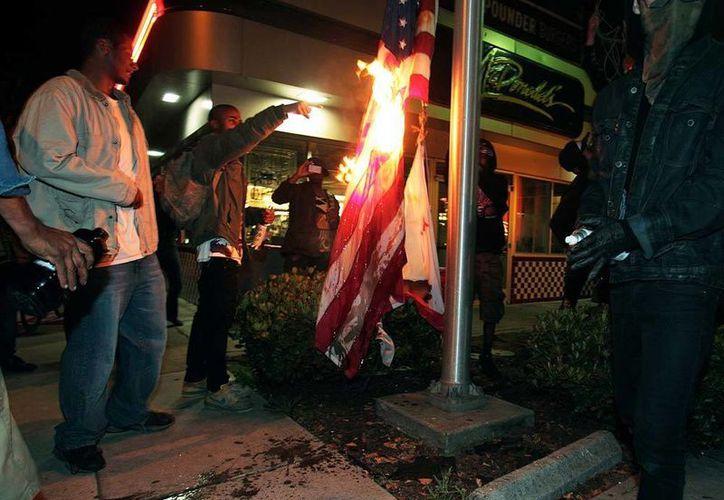 Residentes de un barrio de Oakland queman una bandera de EU, en protesta por la decisión de una corte de absolver a George Zimmerman. (AP)
