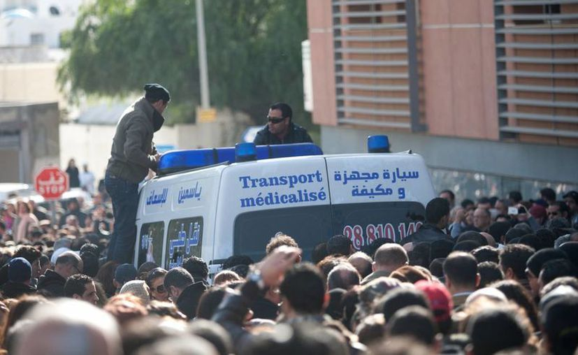 Cientos de personas se reunieron alrededor de la ambulancia que transportaba el cuerpo de Belaid. (Agencias)