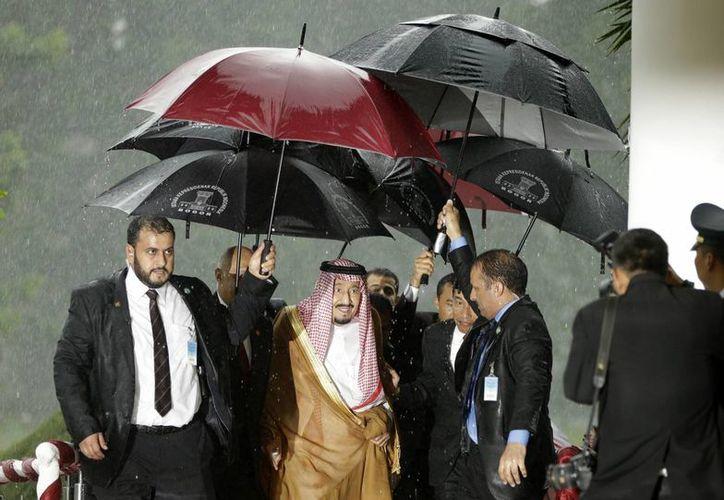 Al menos siete personas de su séquito real cubrían de la lluvia al monarca saudí Salman bin Abdulaziz. (AP/Achmad Ibrahim)