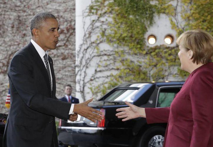 El presidente Obama es recibido por la canciller alemana Angela Merkel antes de una reunión con los jefes de gobierno de Alemania, Francia, Italia, España y Gran Bretaña. (AP/Michael Sohn)