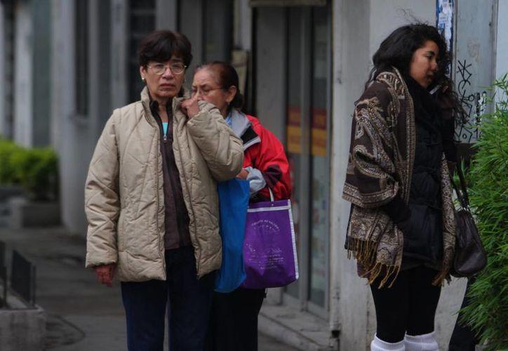 Según el SMN se estiman valores menores a -5 grados Celsius en algunas regiones del país. Imagen de unas mujeres abrigadas caminando por la calle. (Archivo/Notimex)