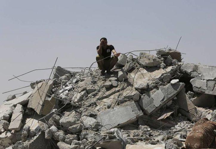 A pesar de los intentos por parar el fuego en la Franja de Gaza, ambas partes del conflicto árabe-israelí reanudaron hoy sus ataques. Imagen muestra a un palestino sobre los restos de una casa destruida en Bureij, un campo de refugiados en la franja de Gaza. (AP)