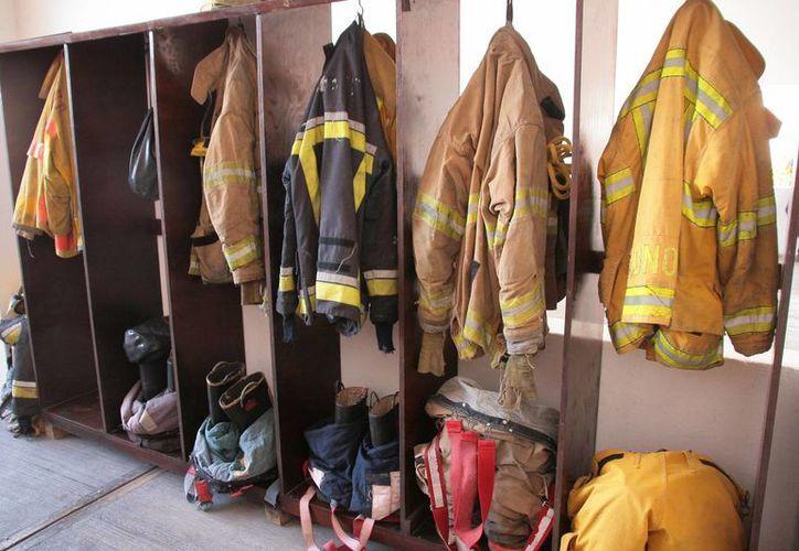 Los uniformes que usaban los integrantes del cuerpo de bomberos de la isla hasta ayer, tienen 20 años de antigüedad. (Irving Canul/SIPSE)