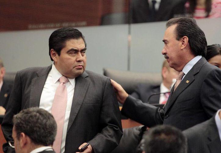 Miguel Barbosa dialoga con Emilio Gamboa en una sesión del Senado. El primero dijo que el periodo extraordinario se hará en dos partes. (Archivo/Notimex)