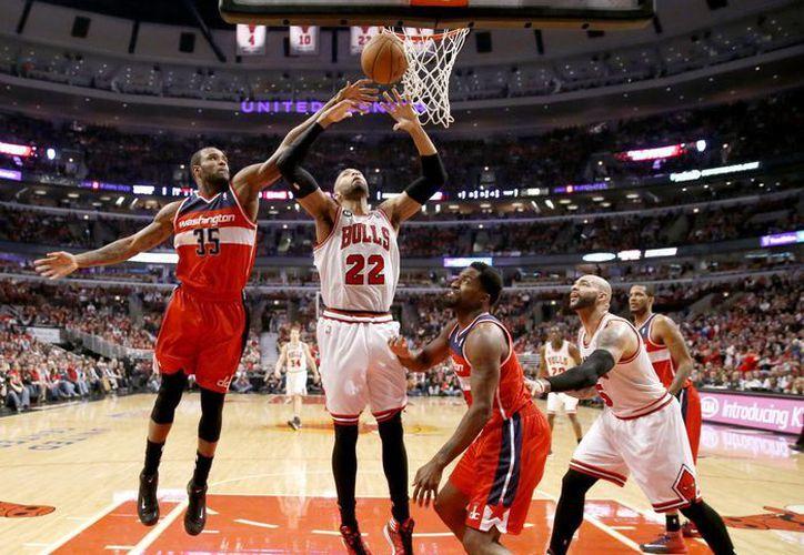 Trevor Booker (35), de Washington Wizards, bloquea un tiro de Taj Gibson (22), de Chicago. (Foto: AP)
