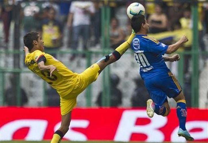 El zaguero del América, Diego Reyes (izquierda), disputa el balón con Danilo Verón, de los Tigres, durante un partido del Torneo Clausura 2013, en la Ciudad de México, el sábado pasado. (Agencias)