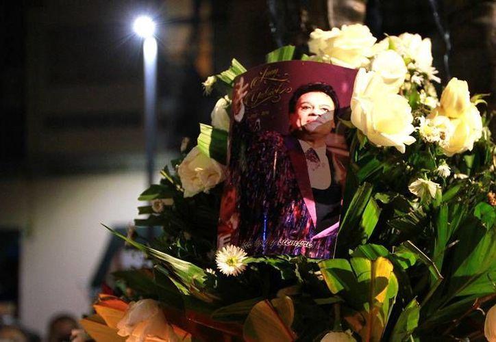 Este martes se reveló que Juan Gabriel enviaría una carta al presidente Peña Nieto, acerca de la situación política del país. En la imagen, una foto sobresale en un ramo de flores en la Plaza Garibaldi, donde 'fans' del cantante, fallecido el domingo pasado en California, le rindieron un homenaje. (Notimex)
