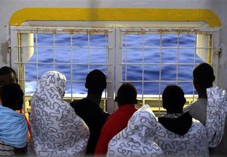 Migrantes miran al mar desde el puente del barco noruego Siem Pilot, mientras viajan al puerto italiano de Cagliari tras ser rescatados en varias operaciones en el mar Mediterráneo. (Agencias)