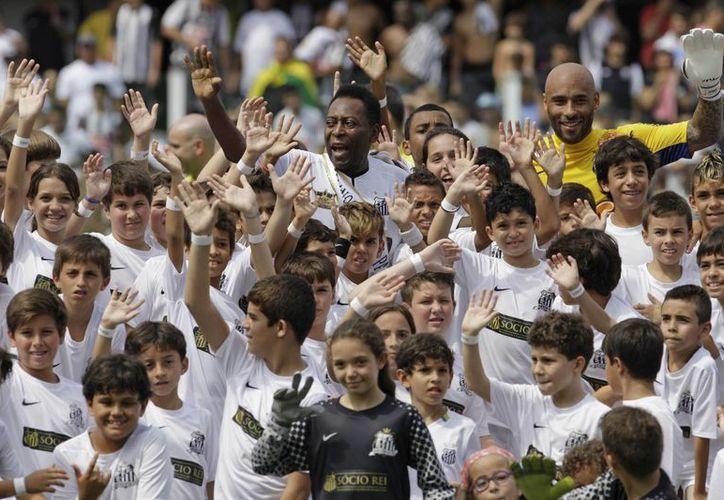 Edinho (al fondo, derecha), hijo de Pelé (al fondo, izquierda), la leyenda del futbol, será detenido por una acusación de narcotráfico. La imagen es de 2012, y corresponde a una ceremonia de los 100 años del club Santos. (AP)