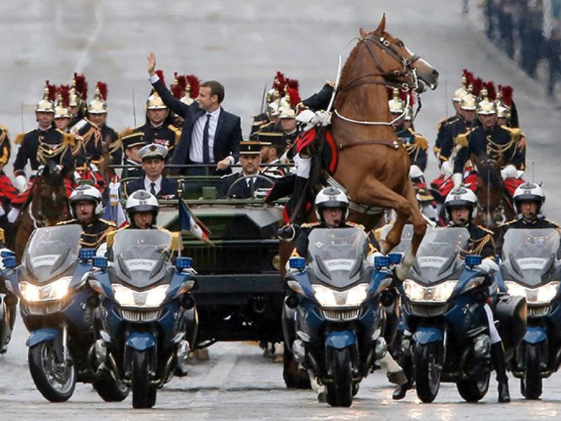 A horse from the horse-riding Republican Guard rears up as new French President Emmanuel Macron waves from a military vehicle.