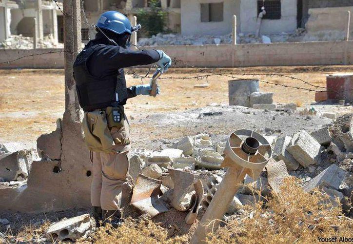 Un miembro del equipo de investigación de la ONU toma una muestra de arena cerca del lugar donde se realizó el ataque con armas químicas. (Agencias)