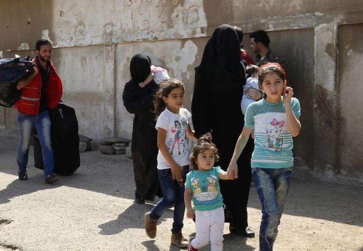 Los convoyes de ayuda humanitaria internacional han sido bloqueados en muchas ocasiones por razones de seguridad. Un grupo de mujeres acompañadas de sus hijos se preparan para salir de Al-Waer, la última zona controlada por los rebeldes de Homs. (AP)