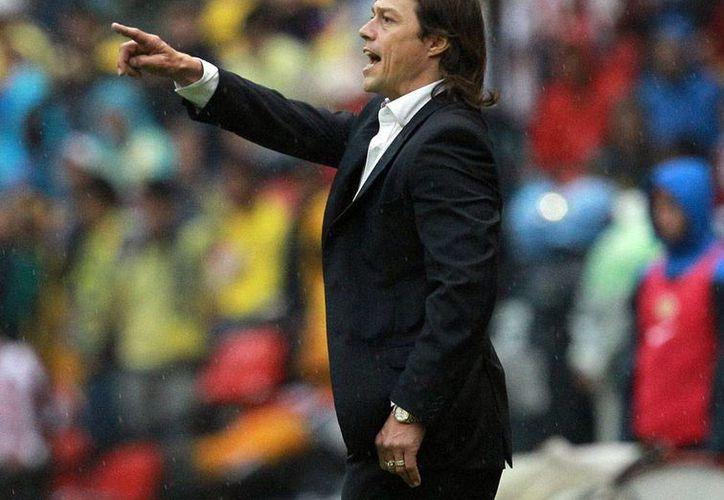 Matías Almeyda, director técnico de Chivas, entró con el pie derecho en lo futbolístico, pero ya dio el primer paso en falso: un video lo muestra fumando en el entretiempo del Clásico América vs. Chivas. (NTX)