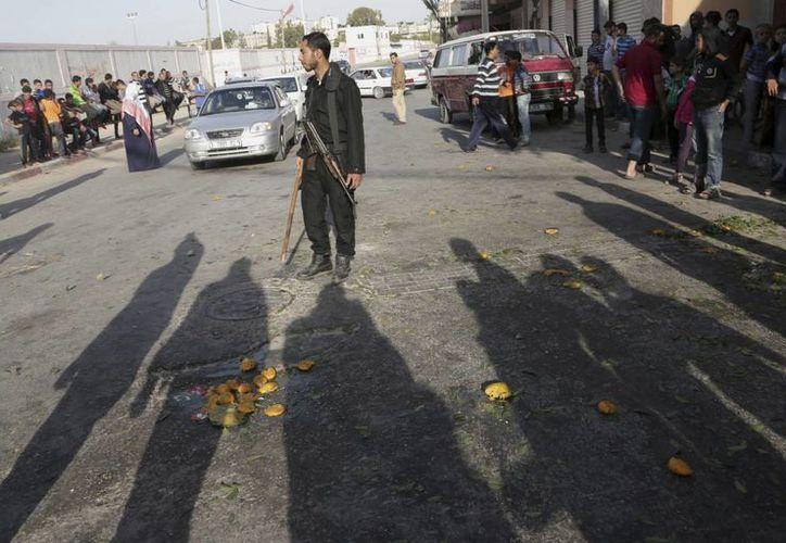 Un guardia de seguridad palestino impide el paso de la gente al lugar de un ataque aéreo israelí en Beit Lahiya. (Agencias)