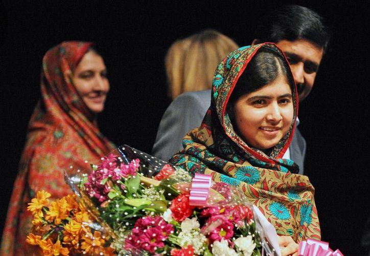 Malala Yousafzai sostiene un ramo de flores después de hablar durante una conferencia de prensa en la Biblioteca de Birmingham, en Birmingham, Inglaterra. (Agencias)