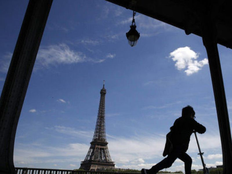A boy rides his scooter on the Bir Hakeim bridge as the Eiffel Tower is seen background in Paris.