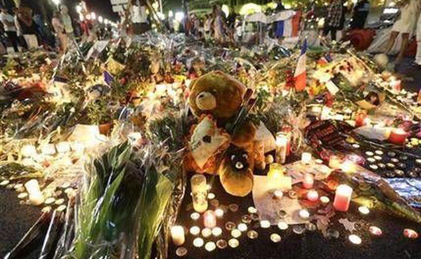 Un oso de peluche rodeado de velas y flores para recordar a las víctimas de un ataque en el Paseo de los Ingleses, cerca de donde un camión arrolló a asistentes a una celebración popular en la calle, en Niza. (AP)