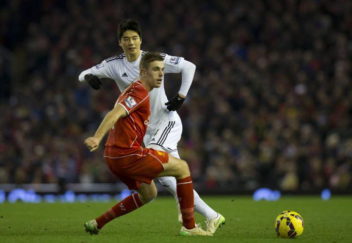 Ki Sung-Yeung, de Swansea, pelea por la pelota con Jordan Henderson, de Liverpool, club que terminó por imponerse 4-1 este lunes en partido de la Liga Premier. (Foto: AP)