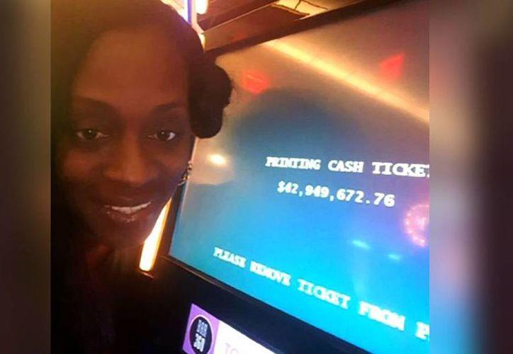 Katrina Bookman se tomó una foto junto a la pantalla para celebrar su millonario premio. Casino dice que fue un error de la máquina. (CNN)