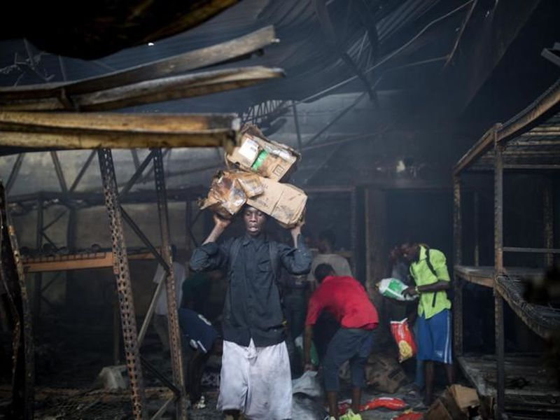 People look for usable merchandise to take from a burned Delimart store, in Port-au-Prince, Haiti.