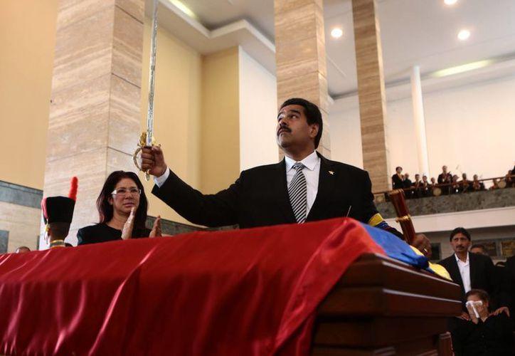 Nicolás Maduro alzando la espada de Bolívar sobre el ataúd de Hugo Chávez. (EFE)