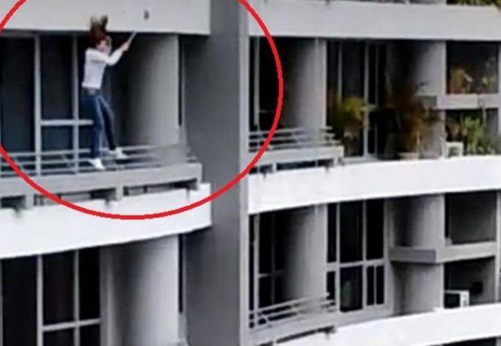 La grabación muestra el momento exacto en que la mujer se precipita al vacio tras ser sorprendida por un fuerte viento. (Excélsior)