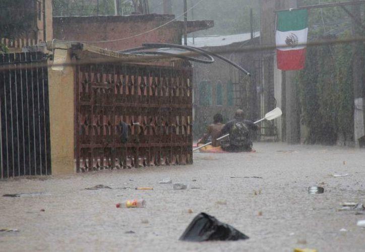 Habitantes navegan en una zona inundada en Acapulco. (EFE)
