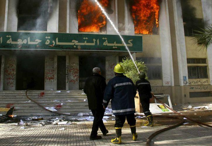 bomberos apagan un incendio en la Facultad de Comercio, que se inició después de que un estudiante fue asesinado bajo circunstancias poco claras durante los enfrentamientos. (Agencias)