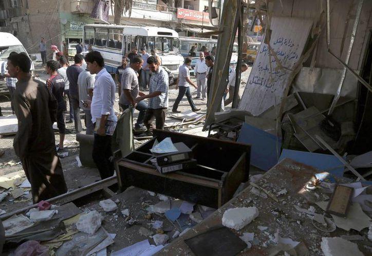 Varias personas caminan en la escena de un atentado con coche bomba en el este de Bagdad, Irak. (EFE)