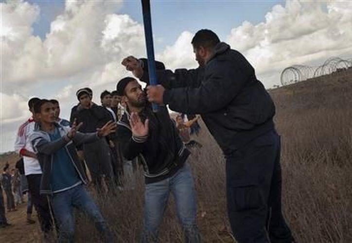 Un policía palestino evita que otros palestinos se aproximen a la frontera en Gaza con Israel, el pasado viernes 23 de noviembre. (Agencias)
