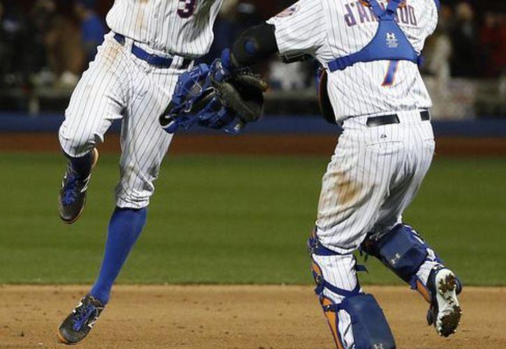 Curtis Granderson (i) celebra con Travis d'Arnaud la victoria de Mets de Nueva York sobre Reales de Kansas City en el segundo partido de la  Serie Mundial. (AP)
